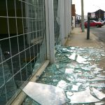 Broken shop window with security screen.